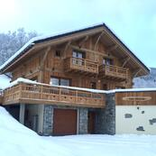 Chalet Les Sauges' exterior with a fresh sprinkling of snow