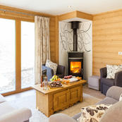 Enjoy picturesque views from Chalet Les Sauges lovely living room & cosy log burner.